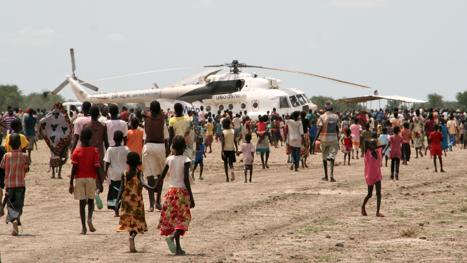 Displaced civilians crowd expectantly around a WFP helicopter in Wau Shilluk, Upper Nile State