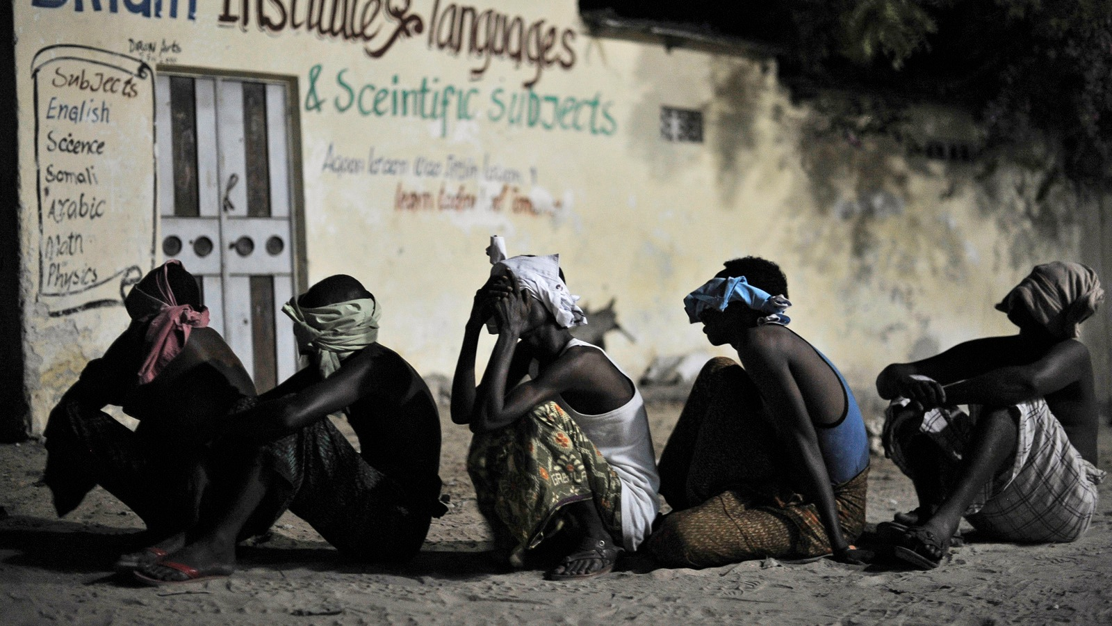 Suspected al-Shabaab militants wait to be taken for interogation during a joint night operation by the Somali security services and the African Union Mission in Somalia (AMISOM), in Mogadishu.