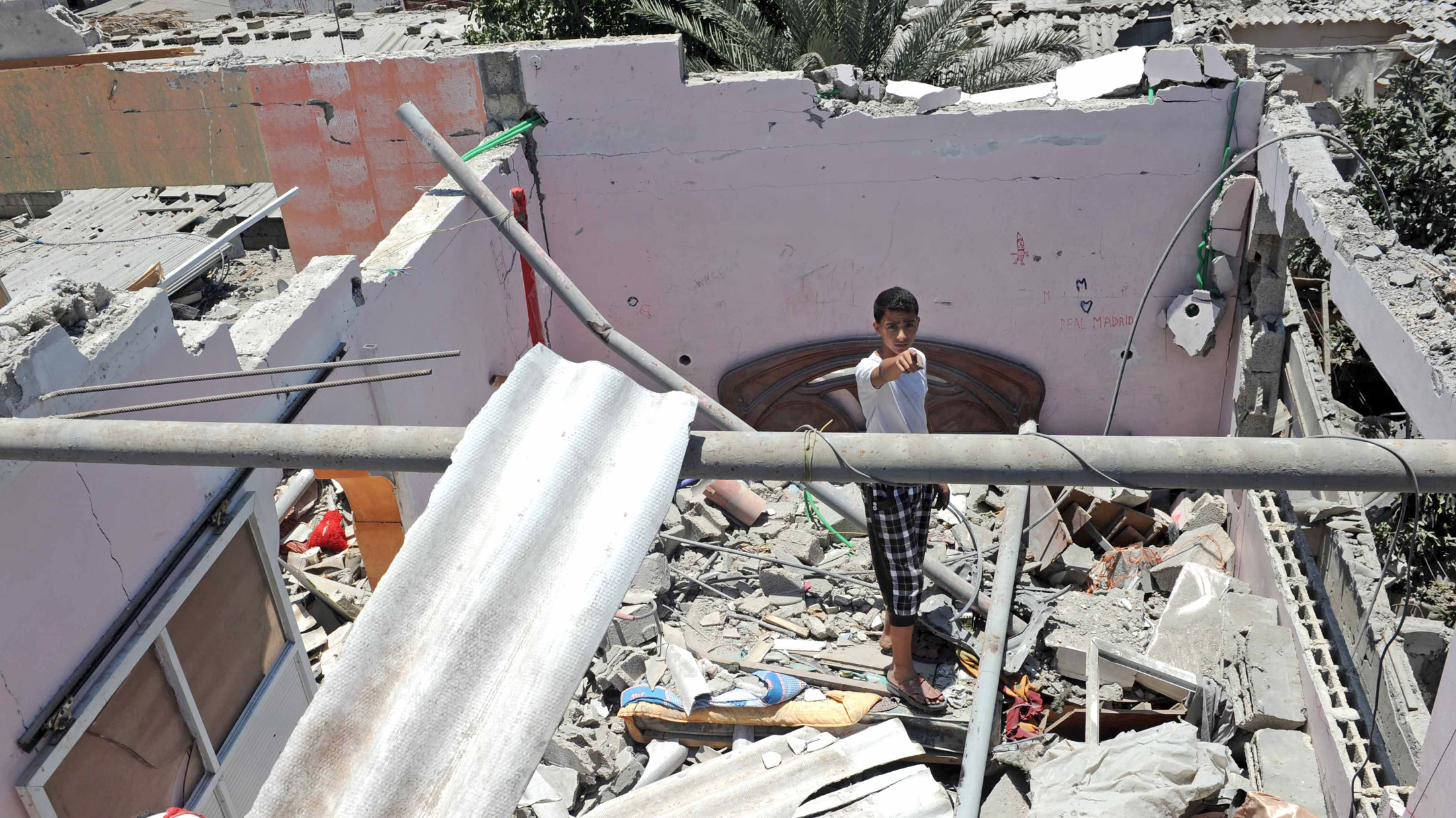 Palestinians inspect the remains of a house which was destroyed during an air strike in Central Bureij refugee camp, in the Middle Area of the Gaza Strip.
