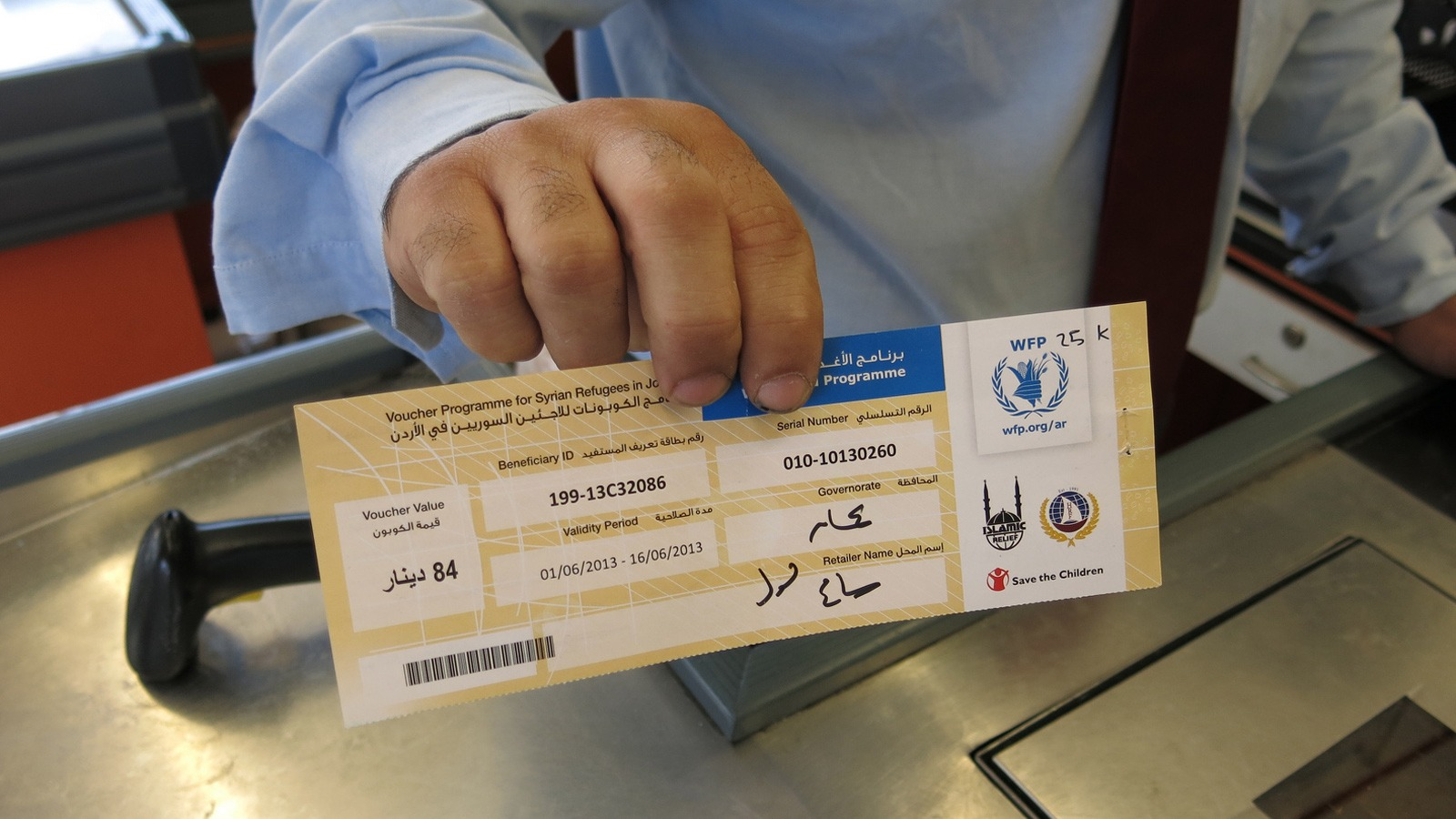 A shopkeeper holds up a WFP food voucher in a supermarket in Jordan