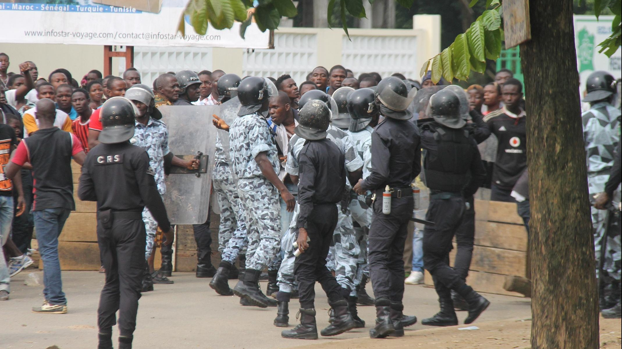 "Ivoirian security forces restrain a crowd protesting against the ""microbes"" youth gang rampaging in the commercial capital Abidjan"