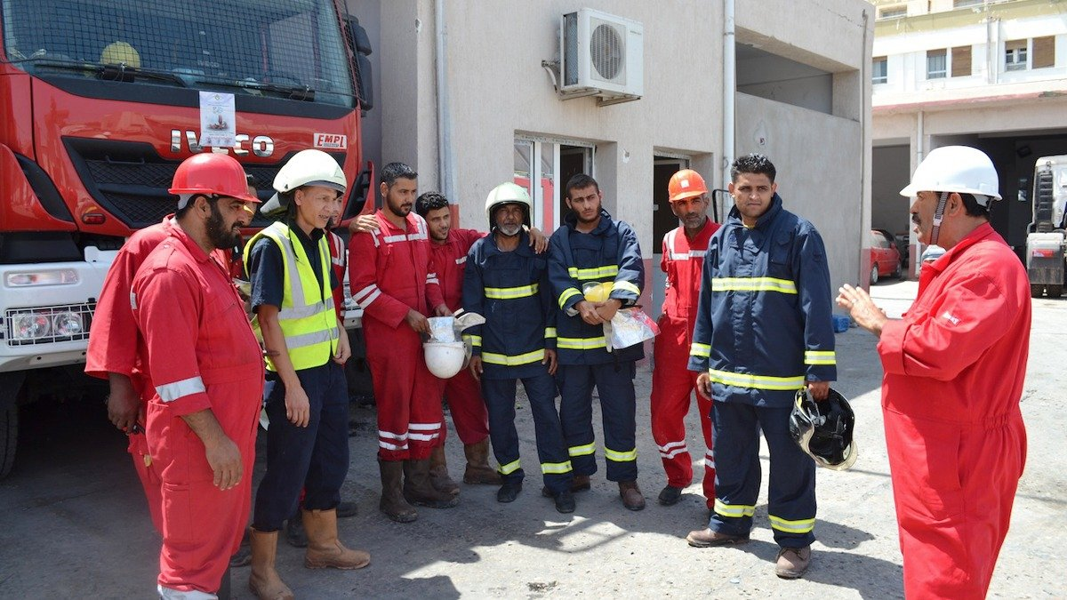 Mohamed Al-Jayer (far right) gives orders to firemen from the main fire brigade in Tripoli.