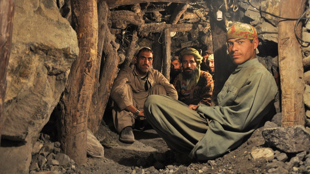 Abdul Hadi, in green turban, sits with fellow miners during a tea break in a rough hewn chromate mine in Pakistan's Balochistan province.
