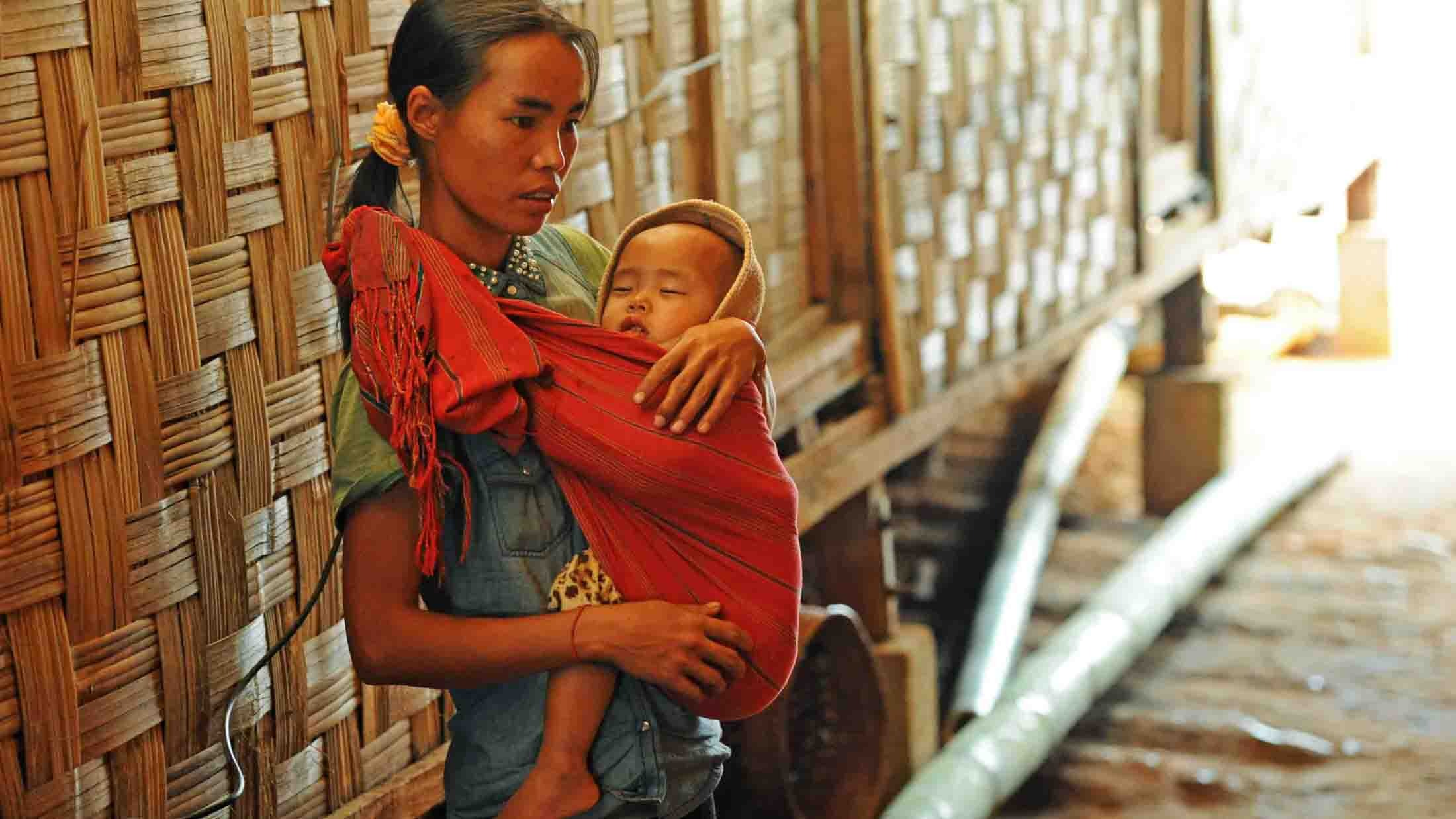 An ethnic Palaung woman carries a child in Nay Win Nee IDP camp in Namkham Township, Shan State.