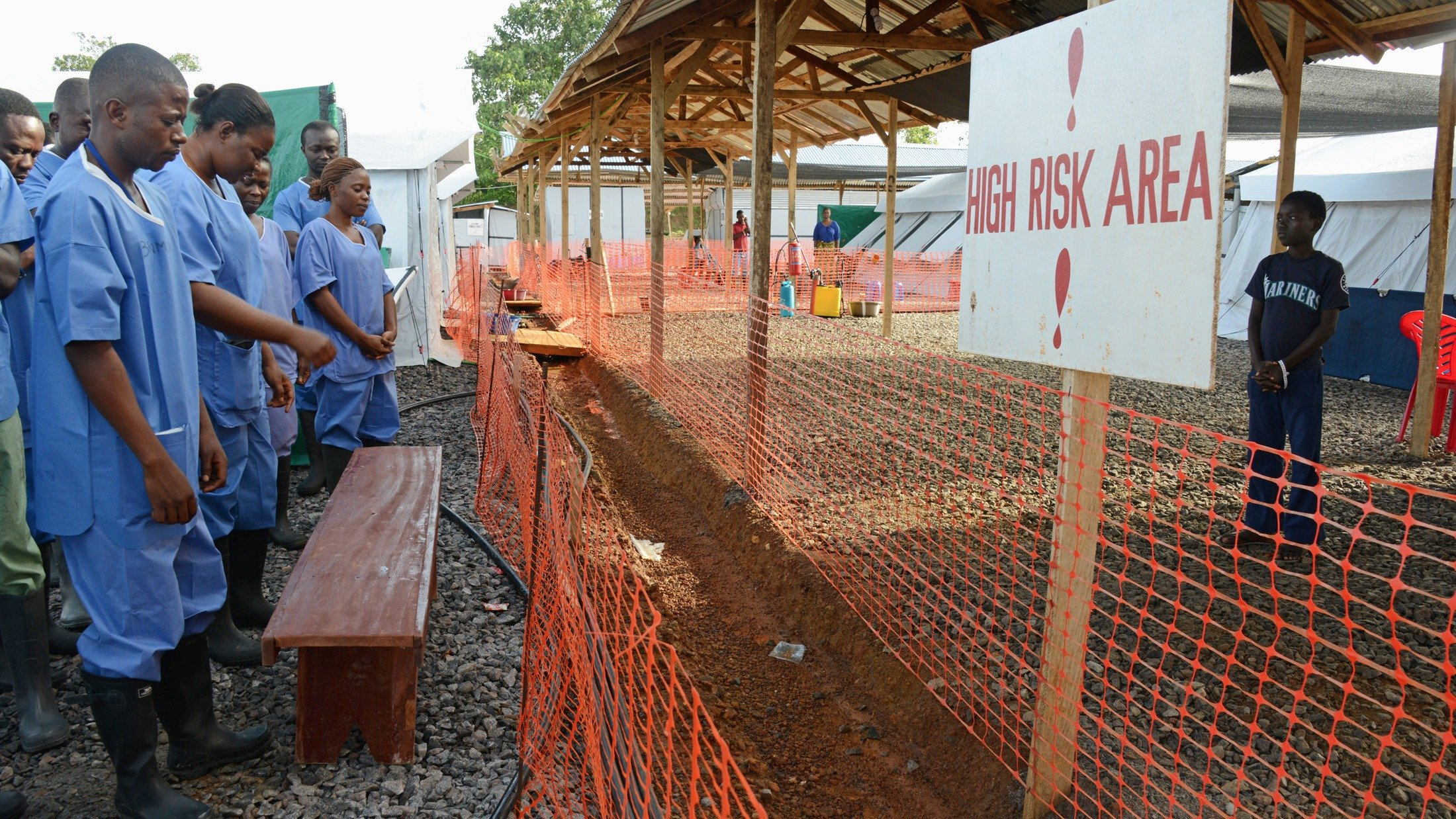 IFRC health workers start the day praying with Ebola patients in the outside area in front of their tents (October 2014)