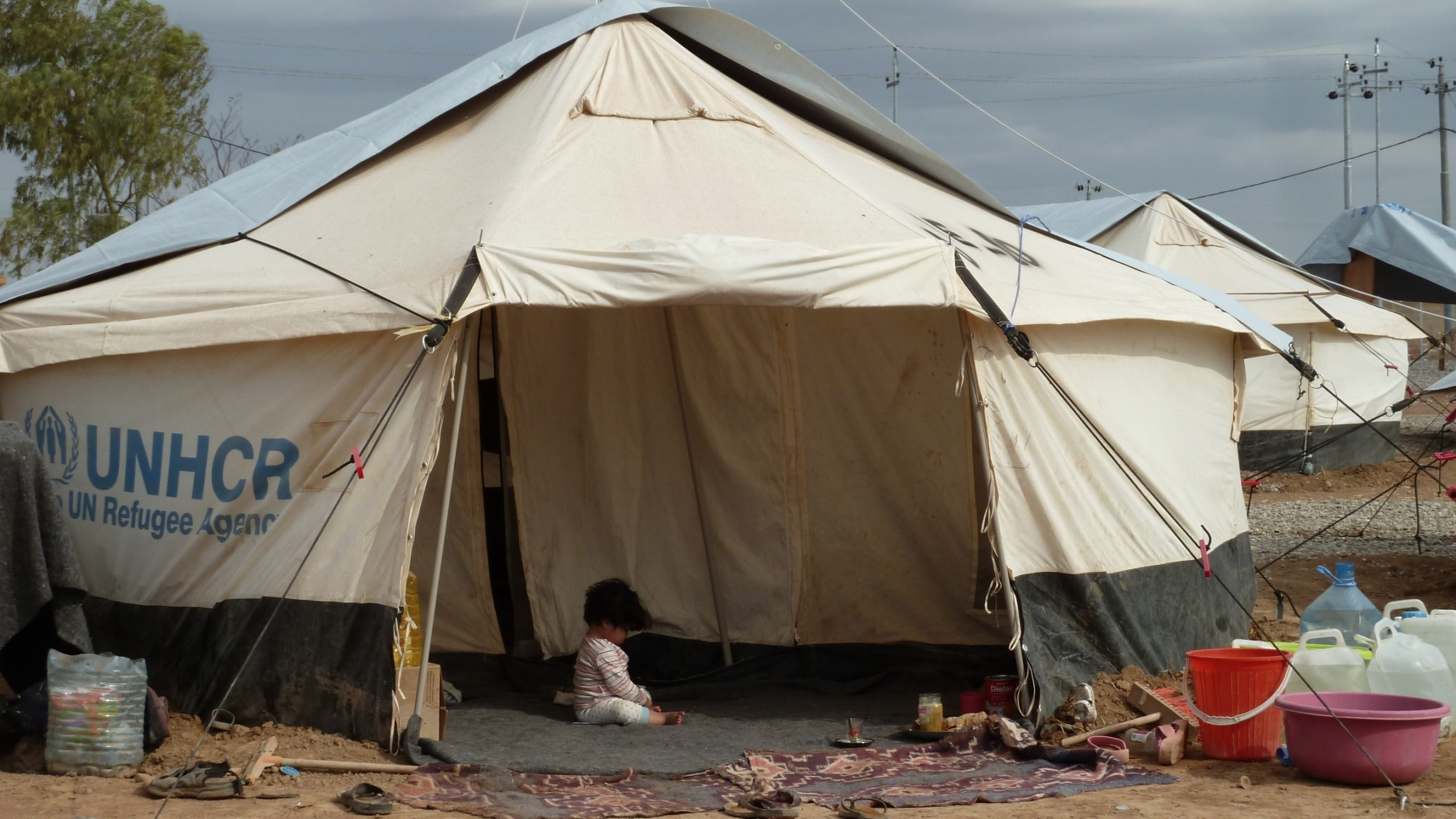 A little girl plays in a tent in Harsham IDP camp, in Erbil, capital of Iraqi Kurdistan. The camp is home to more than 1,000 people displaced by the advance of Islamist militants.  Overhead, storm clouds gather, a reminder of the harsh winter yet to come