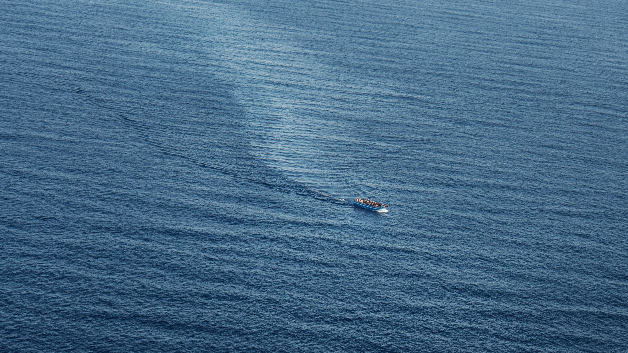 A boat carrying refugees off the coast of Italy in summer 2014. Thousands of refugees attempt to make the perilous journey to Europe every year, with hundreds dying. In the summer of 2014 the Mare Nostrum search and rescue team picked up over 750 a day.