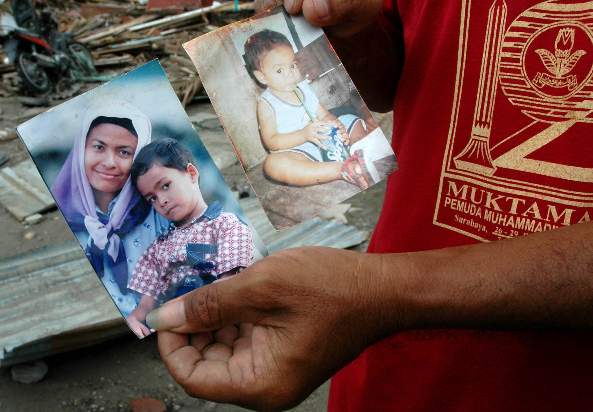 A survivor shares a family photo of those he lost in the Asian tsunami when it hit Meulabboh, West Aceh (file photo 2004)