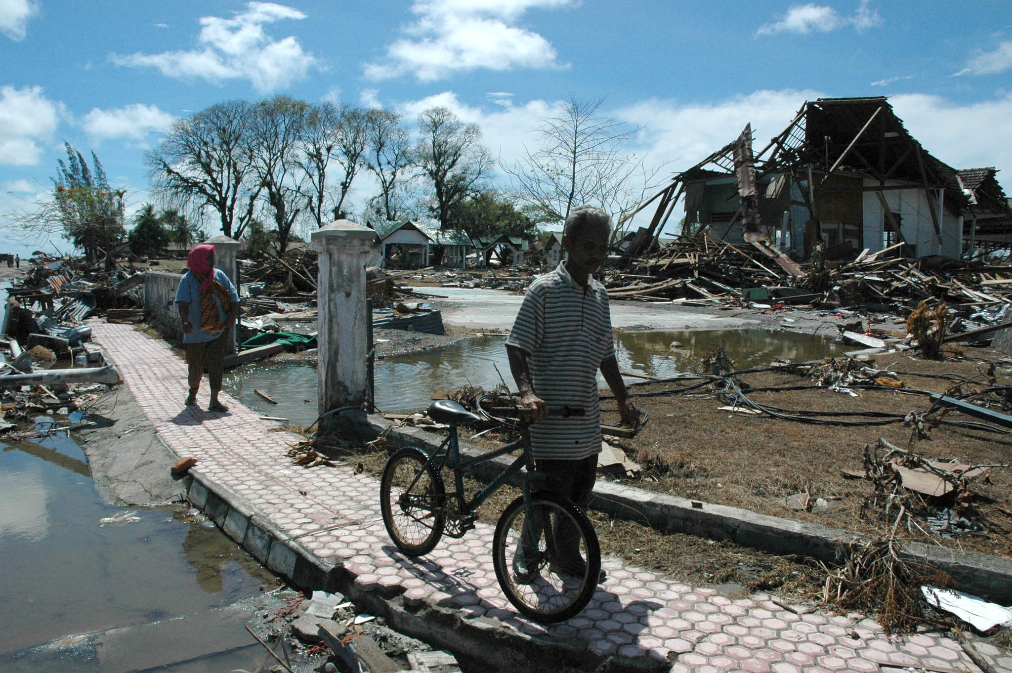 A tsunami survivor walks pass ruins of a building  in Meulaboh, West Aceh (File photo 2004)