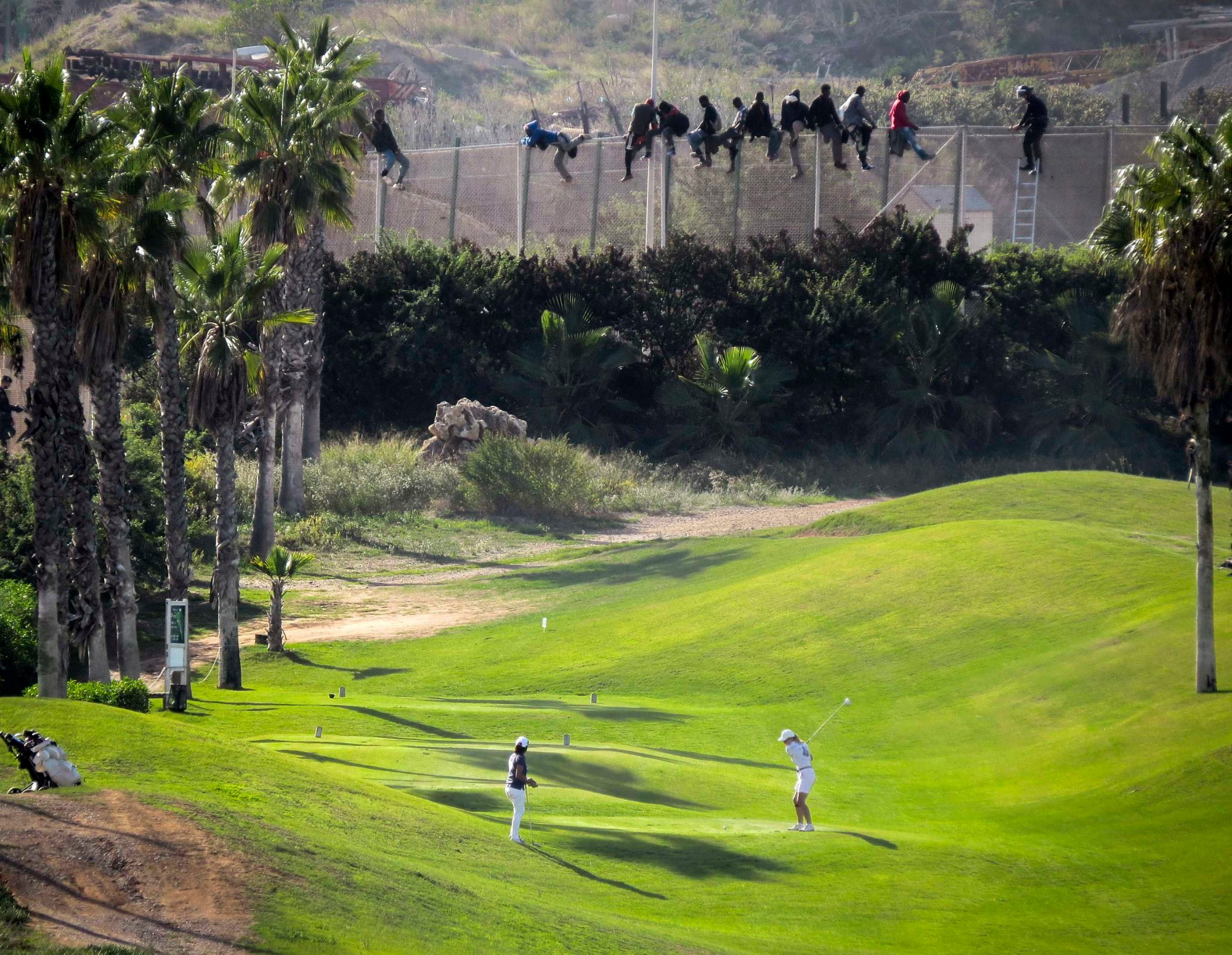 The image of two golfers playing as migrants scale a fence in the Spanish enclave of Melilla, inside Morocco, went viral earlier this year