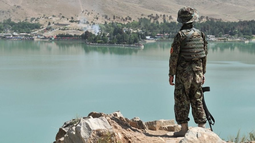 An Afghan National Army (ANA) soldier looks on from a hill near the Spozhmai Hotel following an attack by Taliban militants at Qargha lake on the outskirts of Kabul on June 22, 2012