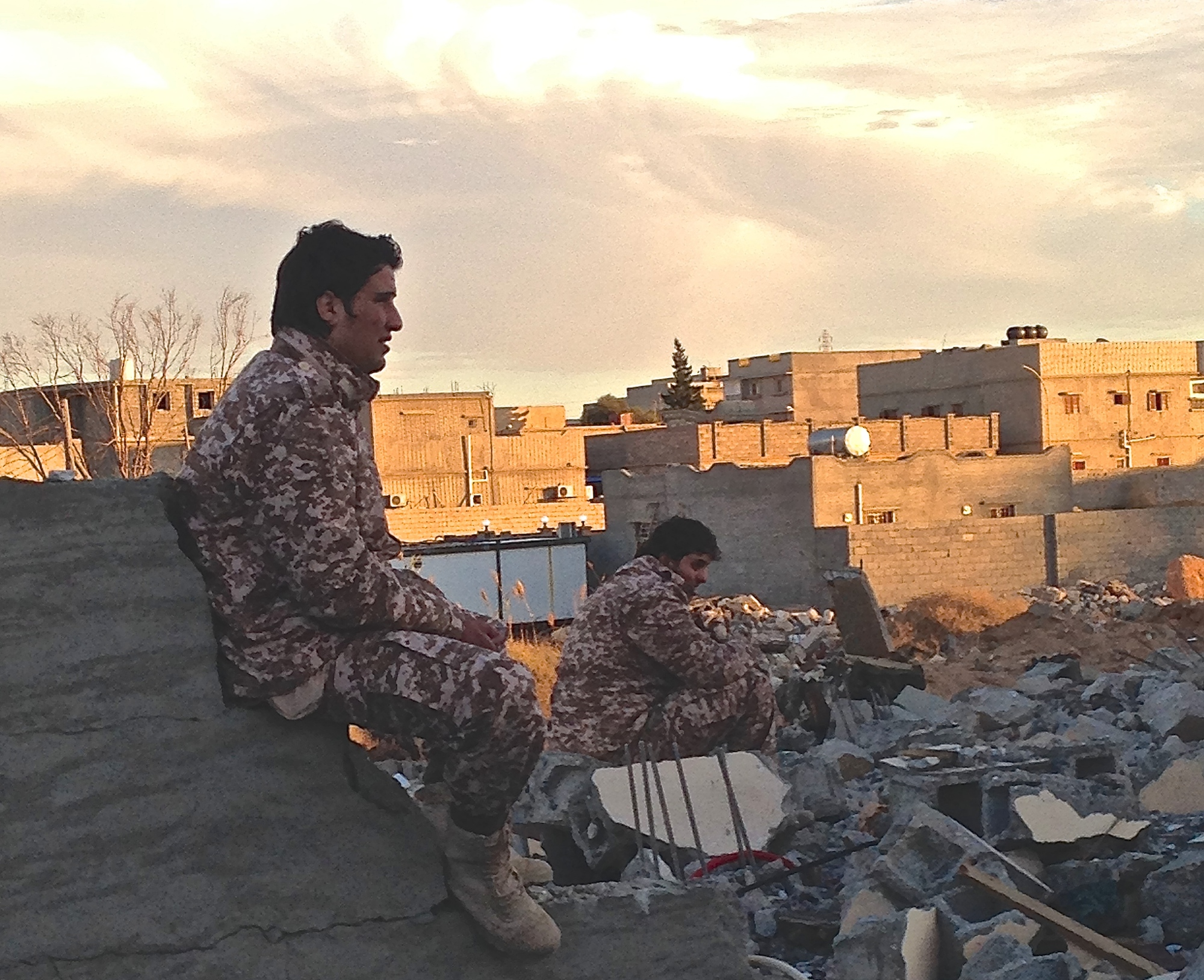 Dusk in the Libyan town of Ben Jawad, where two soldiers from forces operating under the Tripoli-based government sit by the rubble of another flattened home. The front-line, near Es Sidra oil port, is just 30 kilometres away.