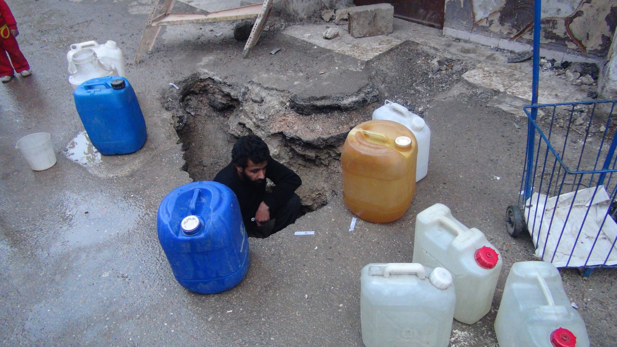 To access water in Yarmouk, the surface of this road was dug up.