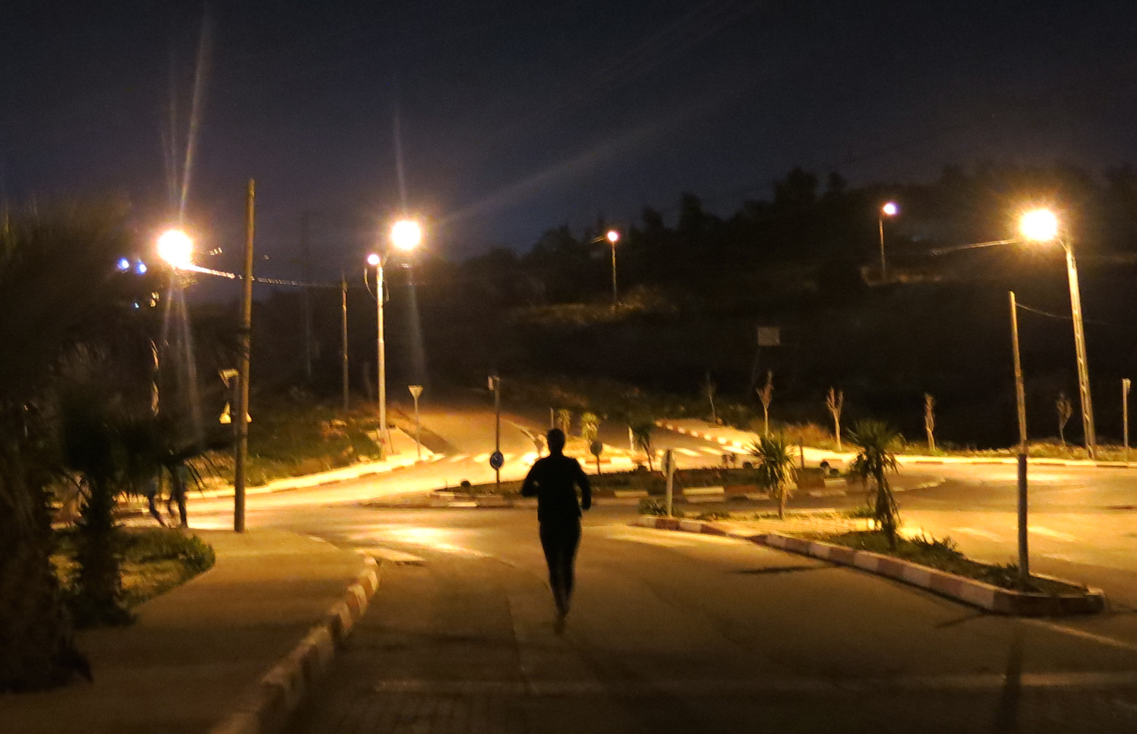 A woman runs late at night near Ramallah in the Occupied Palestinian Territory