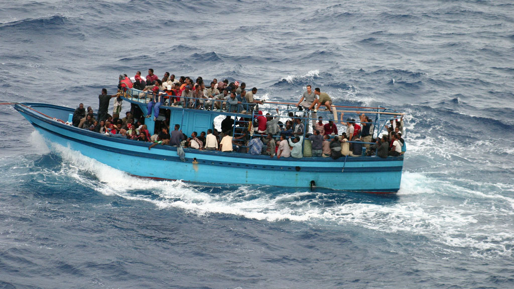 A boat carrying African asylum seekers and migrants in the Mediterranean Sea between Africa and Italy