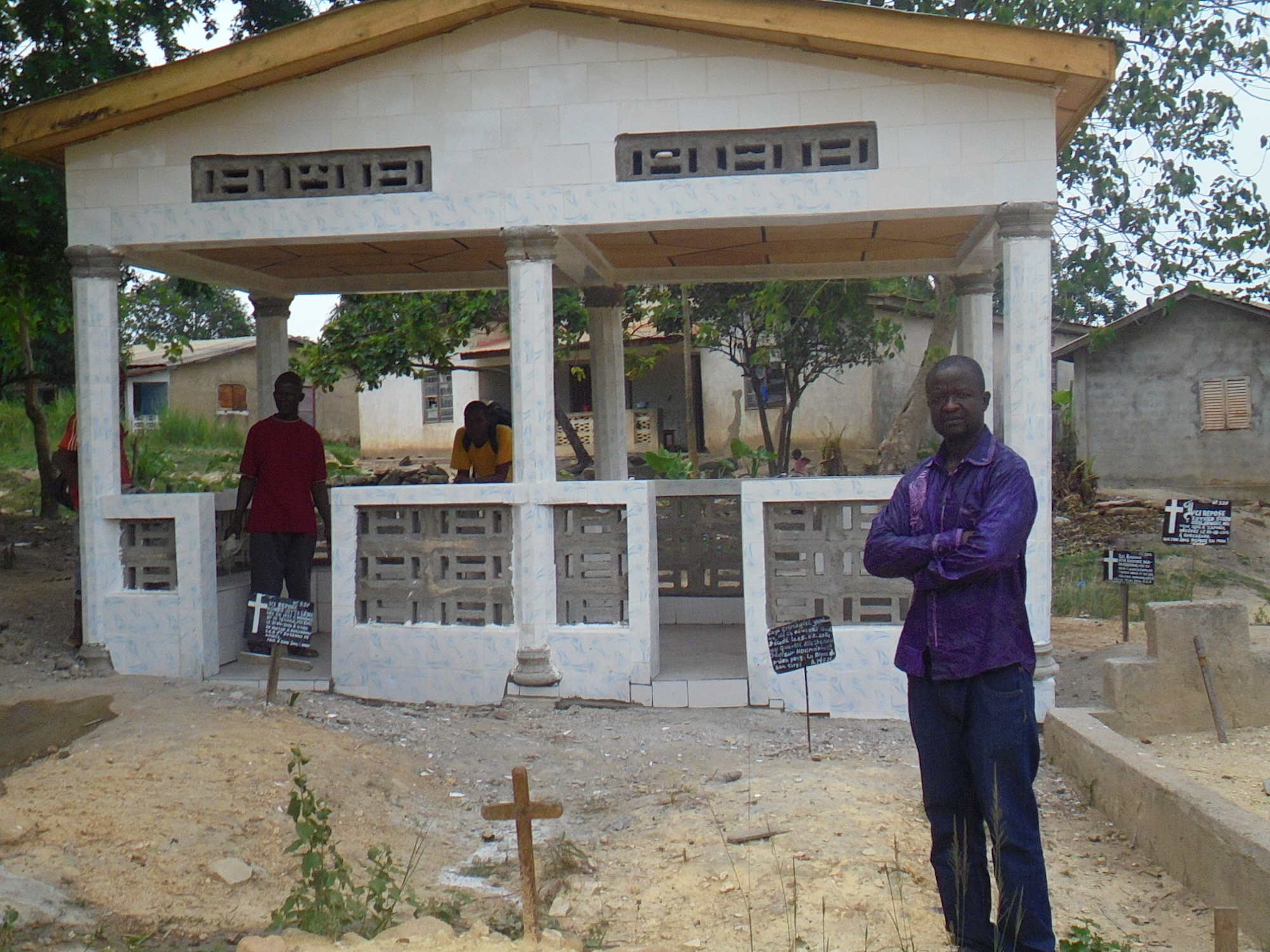 Maurice Ouendeno (on the right) stands outside the memorial sanctuary they built for his father in lieu of having a real burial plot. Guineans, like Maurice, waited more than a year to bury loved ones who had died from Ebola due to the clash between gover