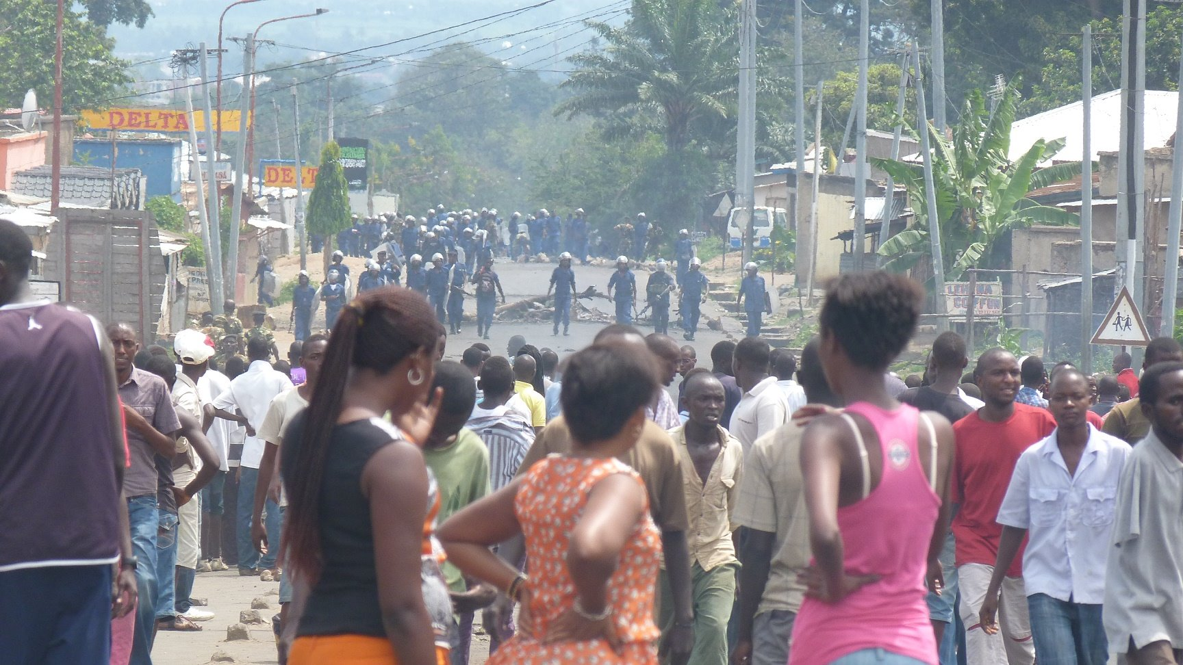 Police look on as people demonstrate in Bujumbura against a decision by Burundi's ruling party to nominate President Pierre Nkurunziza to run for a third term in elections slated for June  2015.