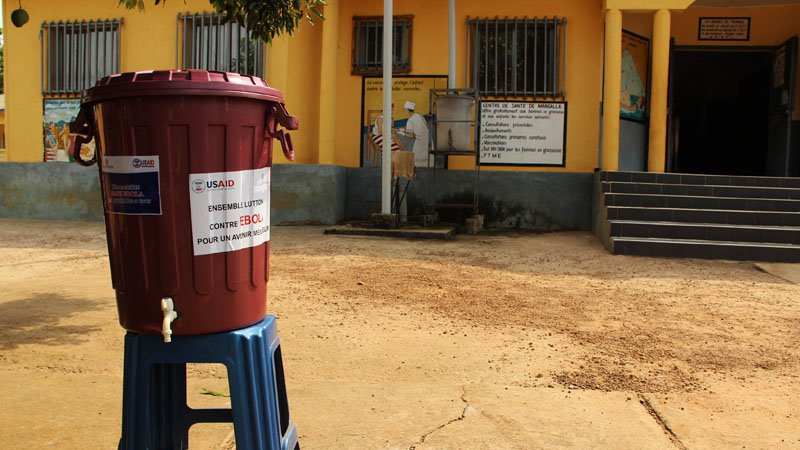 Disinfecting handwashing stations sit outside many buildings and homes throughout Guinea