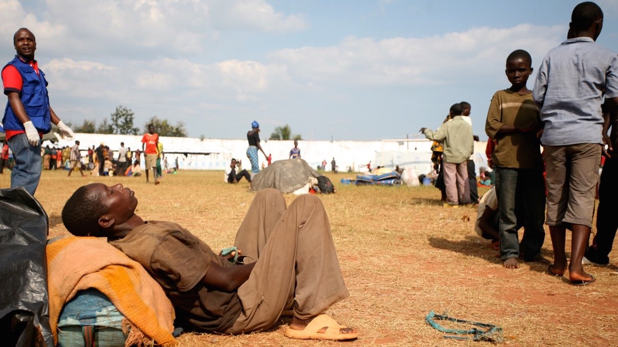 A Burundian refugee dozes in the midday sun at the Lake Tanganyika Stadium, a temporary transit camp for refugees in Kigoma, Tanzania. Tens of thousands of people have been fleeing Burundi amid rising political tensions and a failed coup ahead of election
