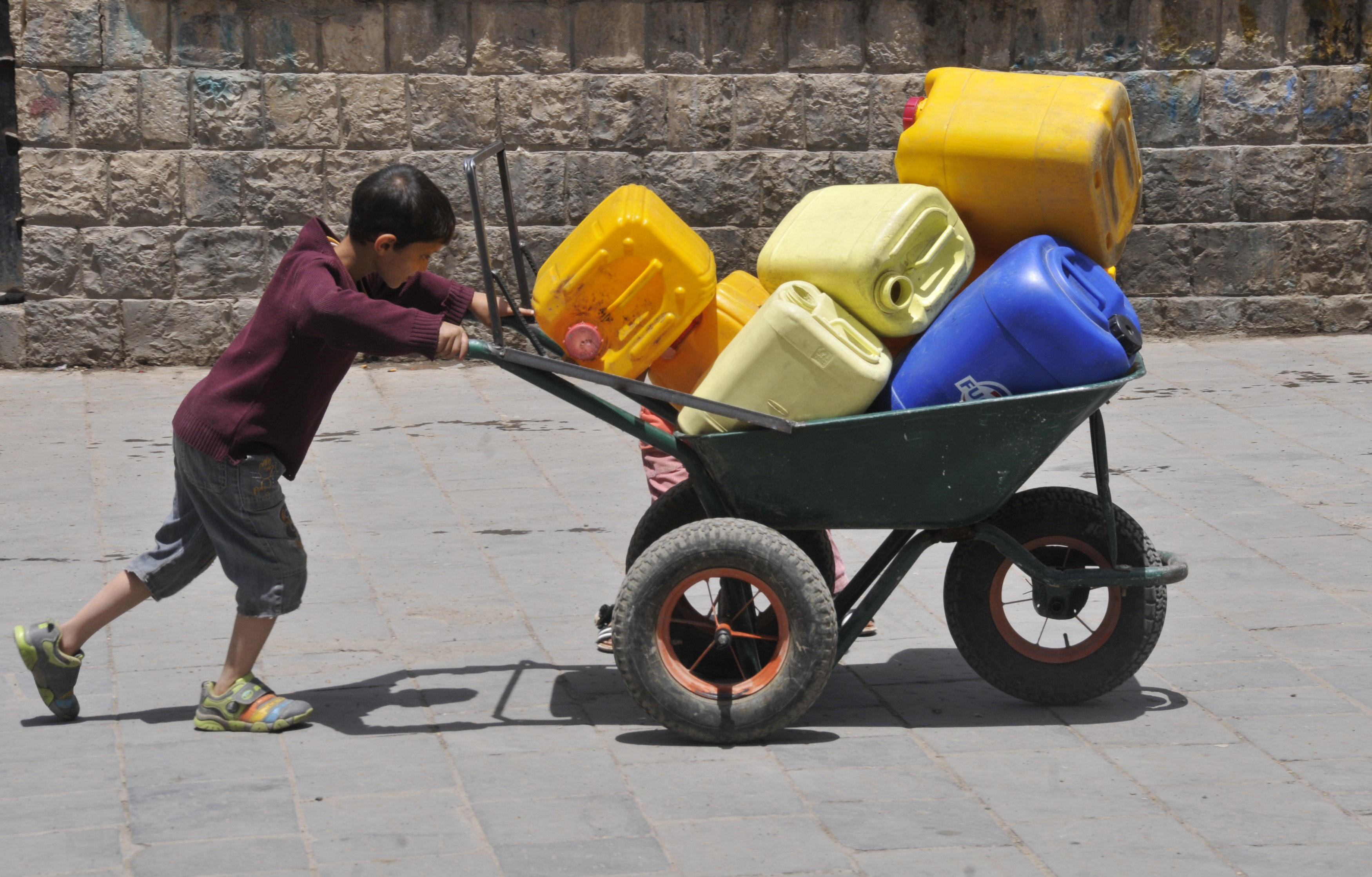 On 11 May 2015, a boy pushes a wheelbarrow filled with jerrycans in Sana'a, the capital of Yemen. 