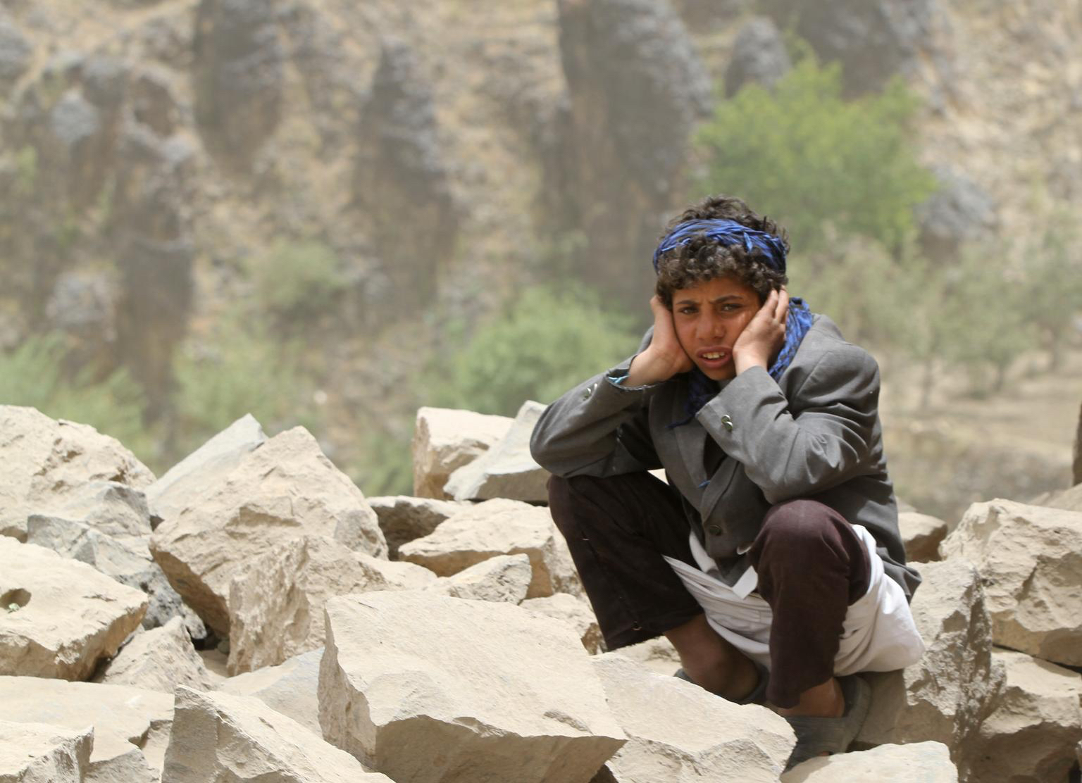 A young boy sits amid rubble all that remains of his home – which was destroyed in an air strike – in Okash Village, near Sana'a, the capital.