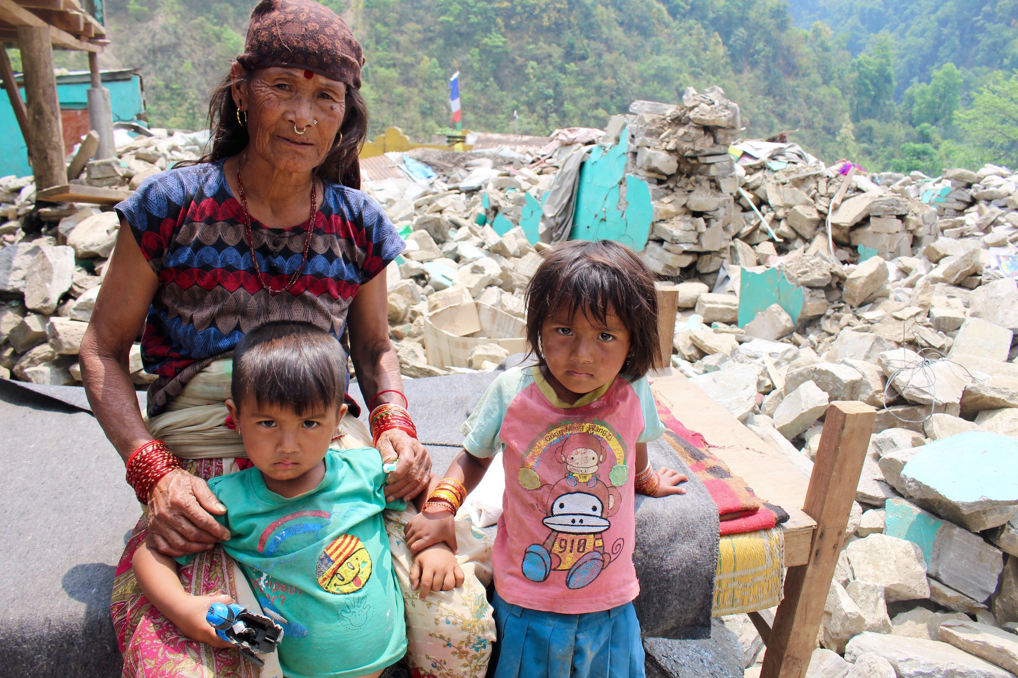 An elderly woman with her grandchildren in the Baluwa market area of Gorkha district, 200 kilometres northwest of Kathmandu. The elderly and children remain most vulnerable to the imminent monsoon season in the wake of the 25 April earthquake that devasta