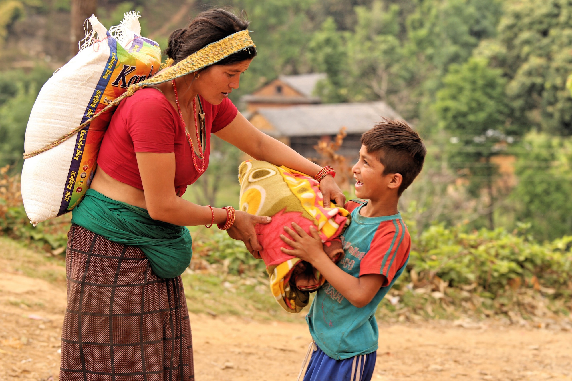 A displaced mother walked for hours with her son to get food relief and a blanket in the village of Kharanitar in Nepal's Nuwakot district. Supplies are often dropped far away from remote villages