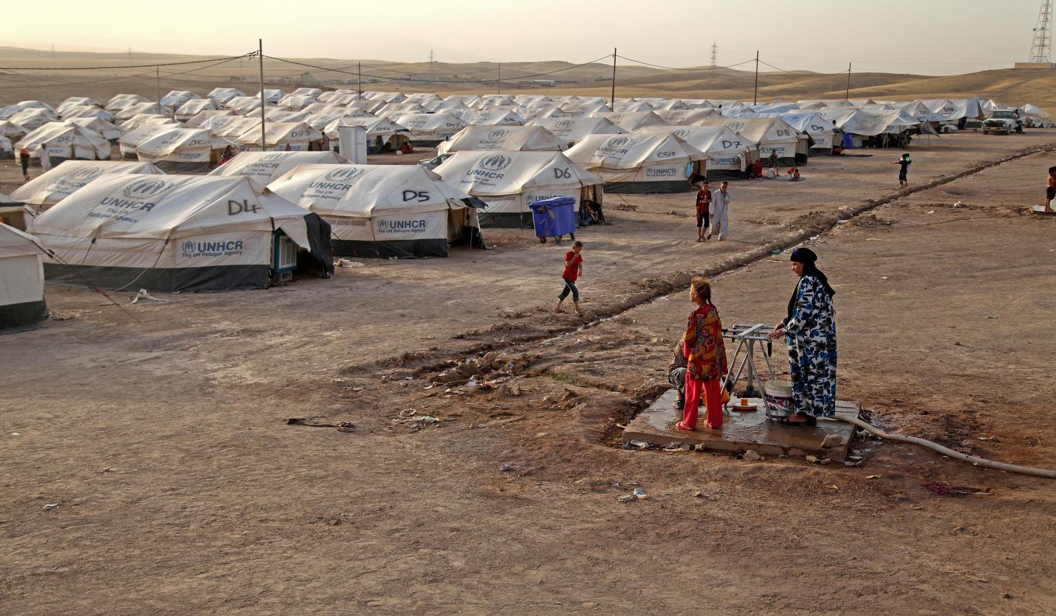 On 29 June 2014 in Iraq, displaced women fill containers at a water point, near rows of tents, in the Khazar transit camp in the northern-eastern city of Erbil. The camp received IDPs from Mosul but has since been disbanded due to fighting in the areas