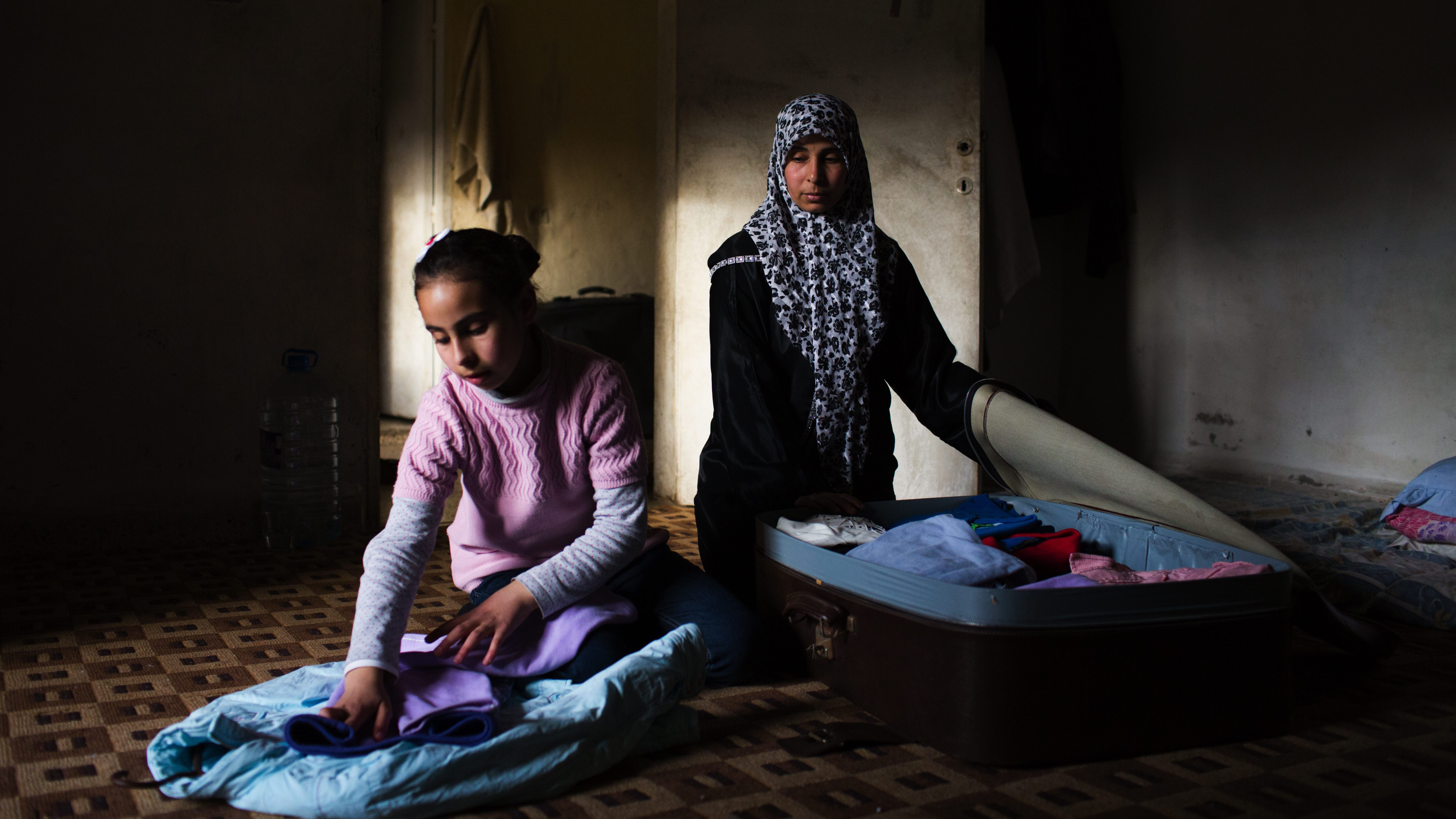 Syrian Refugees, Um Abdullah and her daugther Maysaa, 13, pack a suitcase in preparation for their journey to Gemany, at their temporary home in Barja, Lebanon in April 2014. The family will travel to Germany under the resettlement programme.