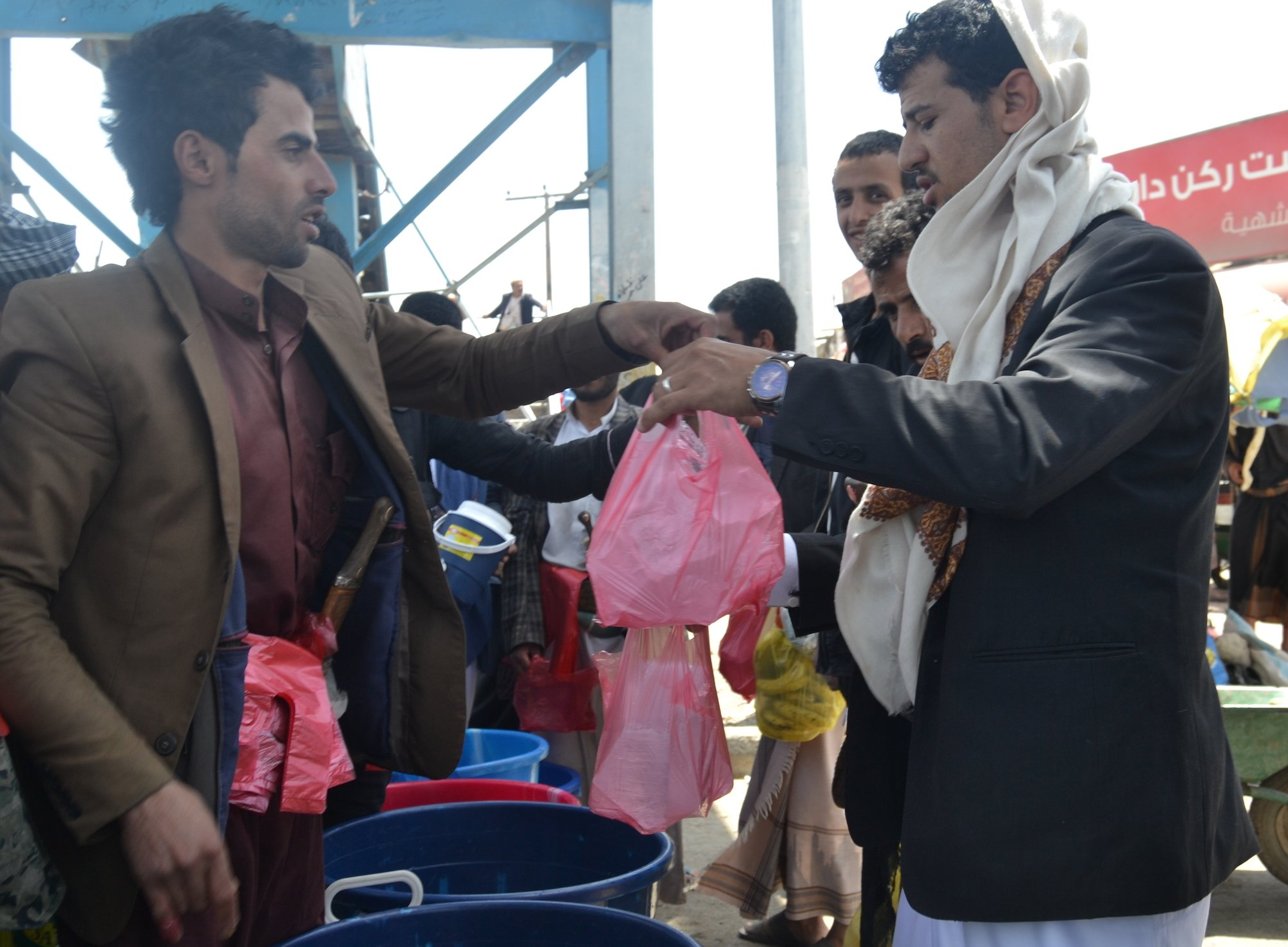 Men buy and sell bags of ice in the Yemeni capital Sana'a during a sustained Saudi Arabian-led bombing campaign