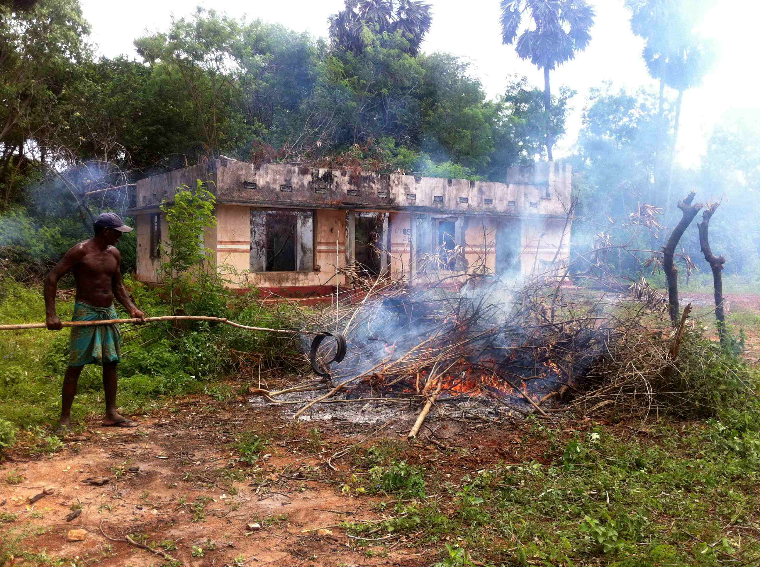 A man burns debris in front of a destroyed house on land returned to civilians by the military in Tellipallai, northern Sri Lanka