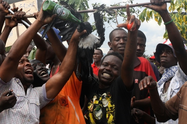 Protestors in the Bujumbura neighbourhood of Musaga pretend to feed beer to a dead bird that is intended to represent, and to denigrate, Burundi's ruling party, whose symbol is an eagle.