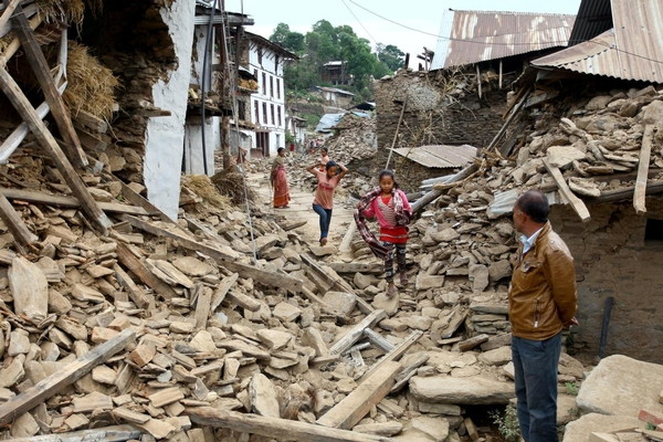 On 16 May, a man and two women look on as two girls run through a street lined with the rubble of destroyed houses in Bhimeshwar Municipality, Dolakha District, the epicentre of the 12 May earthquake