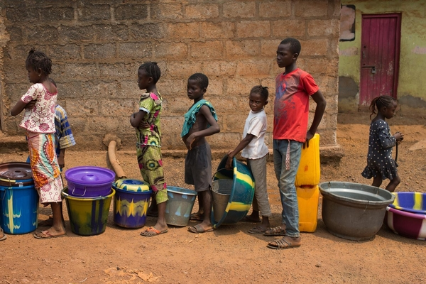 Children queue with containers to receive with water, in the city of Kenema in Kenema District, Sierra Leone.  March 2014
