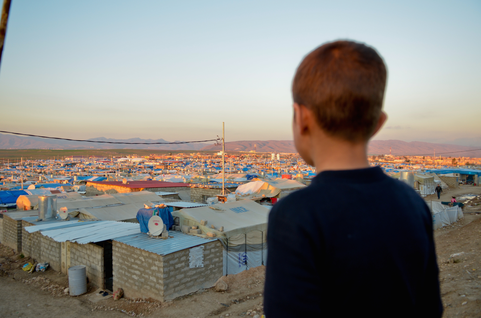 A displaced Iraqi child stares out at his IDP camp in the northern Kurdistan region