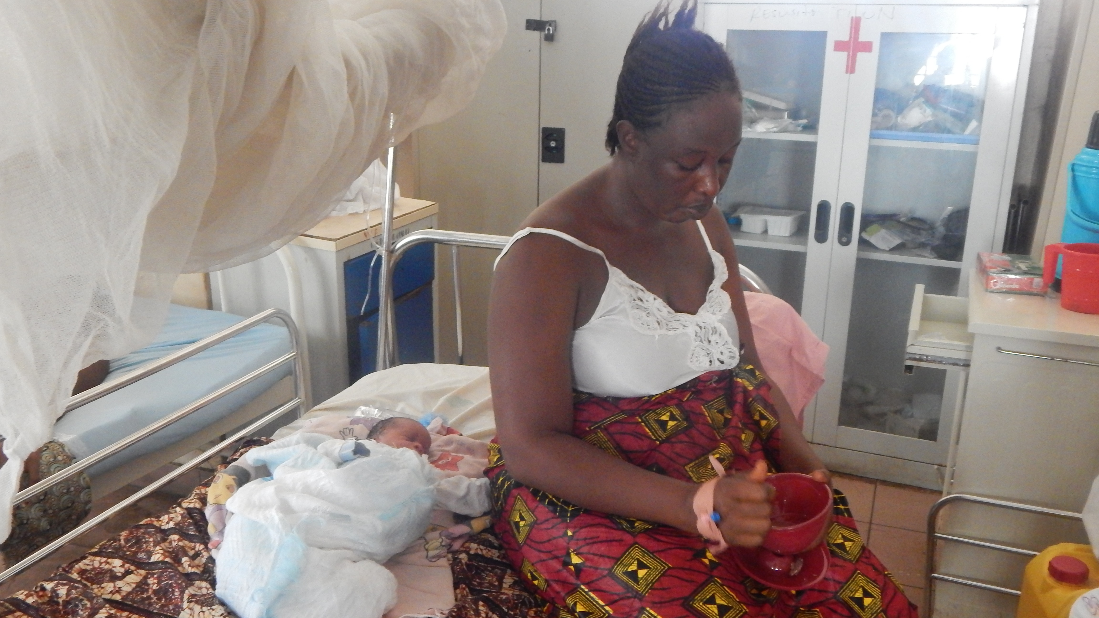 Aisha Kargbo sits besides her newborn child at the PCMH (Cottage) Hospital in Freetown.