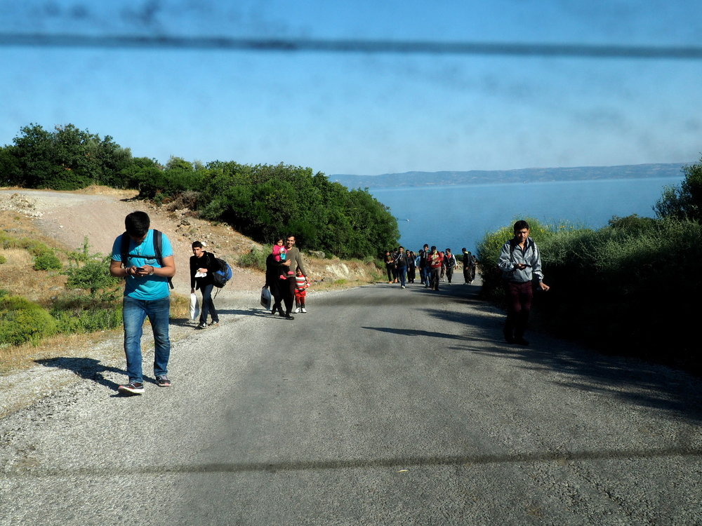Migrants begin the 60 kilometre trek from Skala Sykaminias to Mytilene. Locals who offer them lifts risk being charged with human smuggling. Greece.