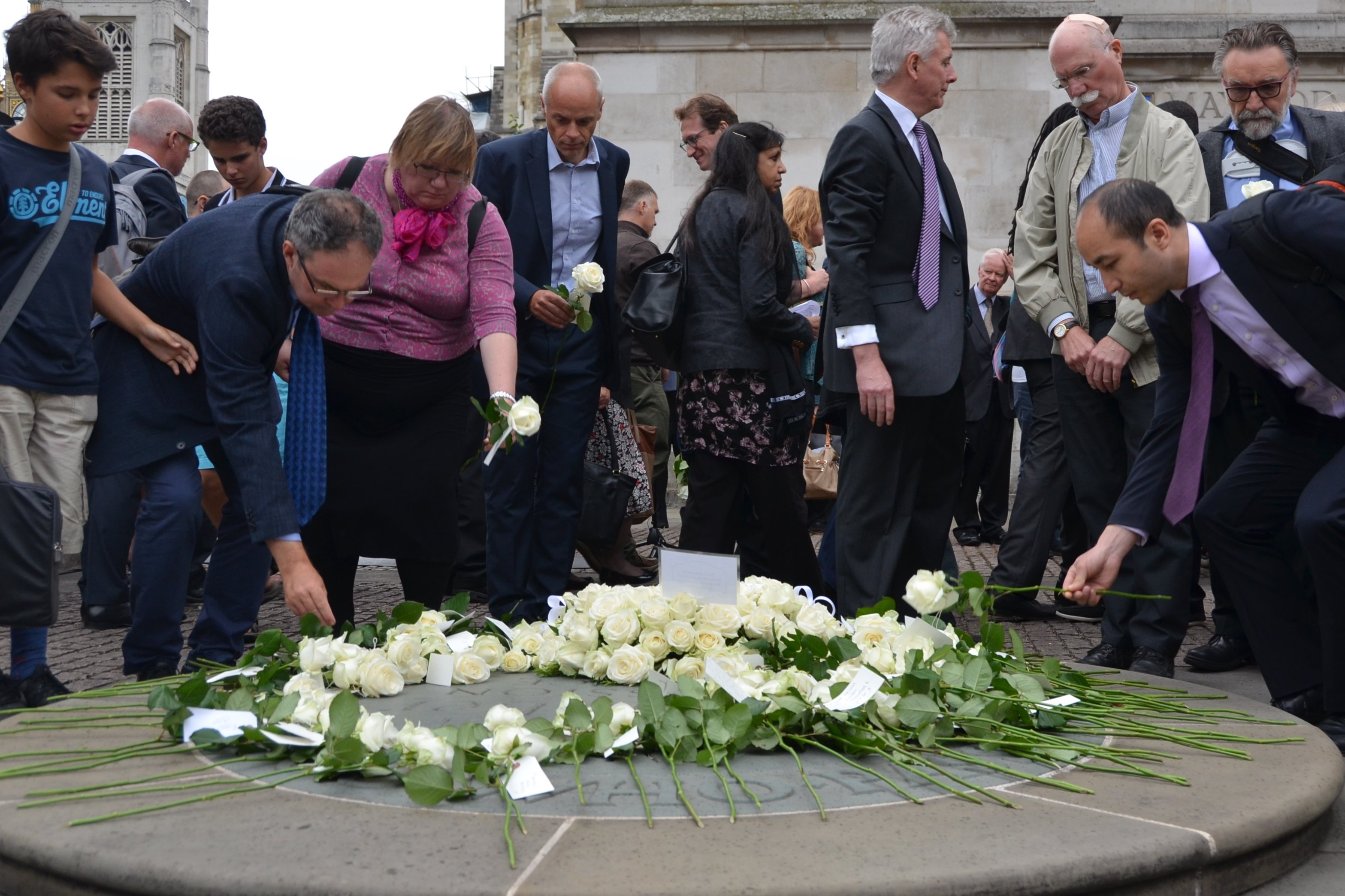 Friends, family and colleagues of aid workers killed in the course of humanitarian work lay a rose with the name of their loved one during a memorial outside Westminister Abbey in London on 18 August 2015 in the lead-up to World Humanitarian Day.