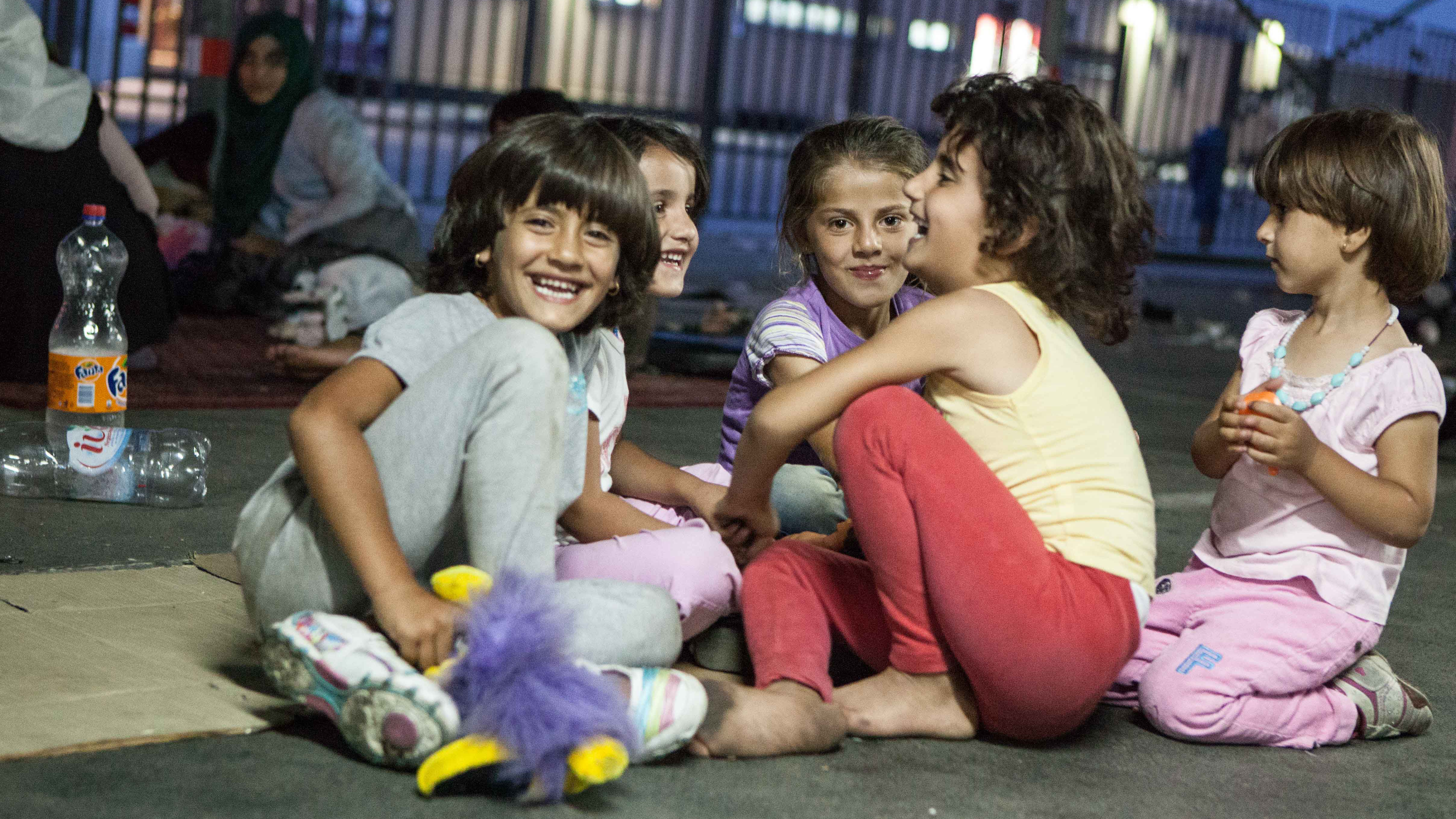 Syrian girls play at a car park in Belgrade where they are staying until their families can organize transport to the Hungarian border