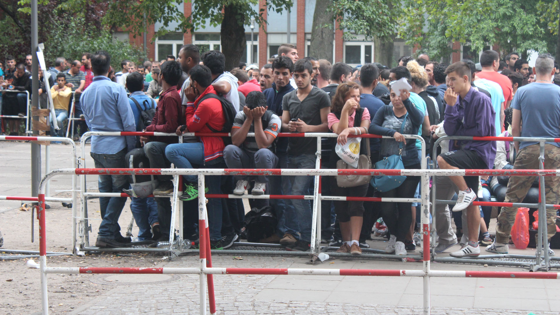Recently arrived asylum seekers queue up to register with the Berlin State Office of Health and Welfare in Germany on 27 August, 2015