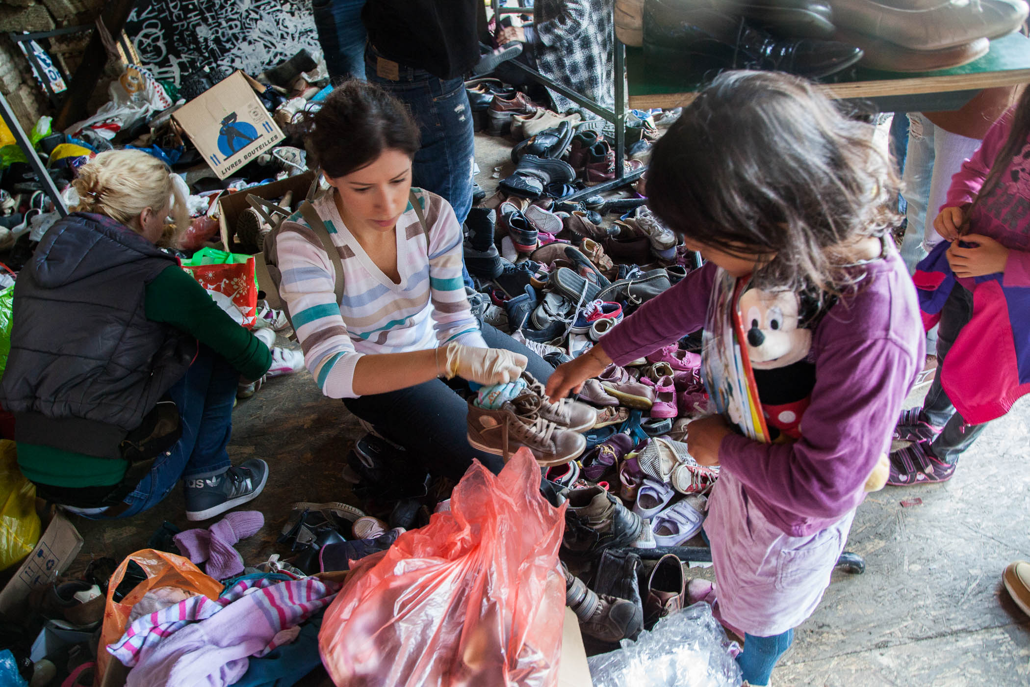 A volunteer helps a young Syrian girl find new shoes and socks at Miksaliste, a hub for the refugee response in Belgrade, started by Refugee Aid Serbia, an umbrella group of local charities
