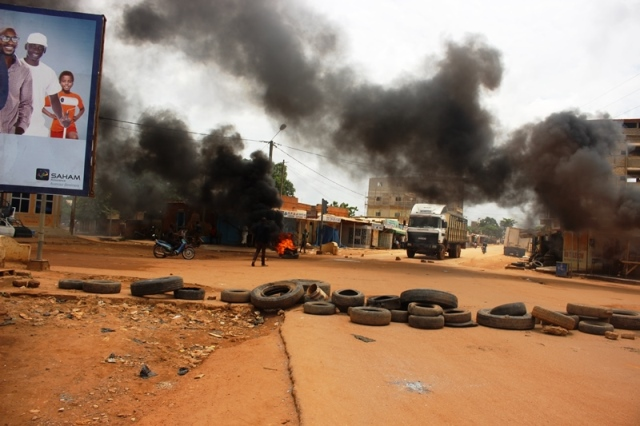 Protesters burn tires on roads to stop the military from passing in Ouagadougou