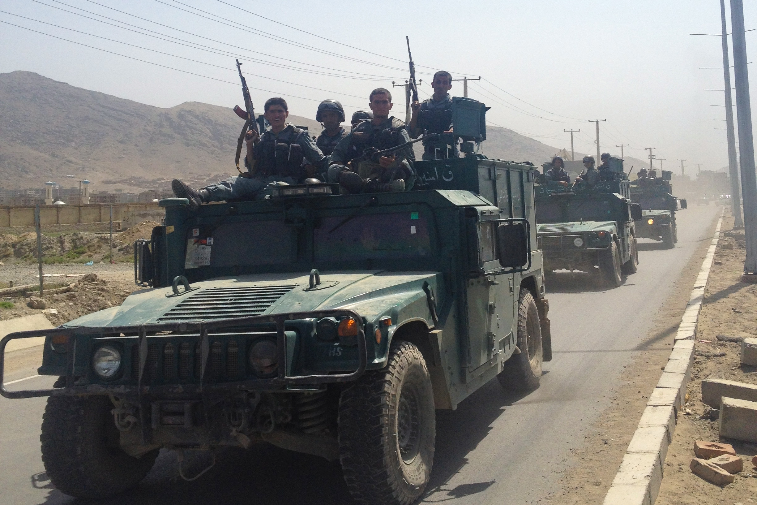 Afghan security forces travel in convoy after leaving the site where four insurgents launched an attack on Kabul airport, 17 July 2014.