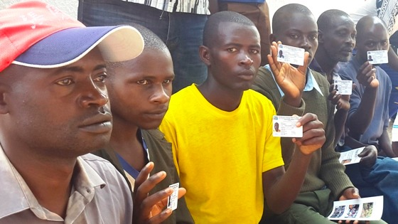 Former members of armed groups display their demobilisation cards