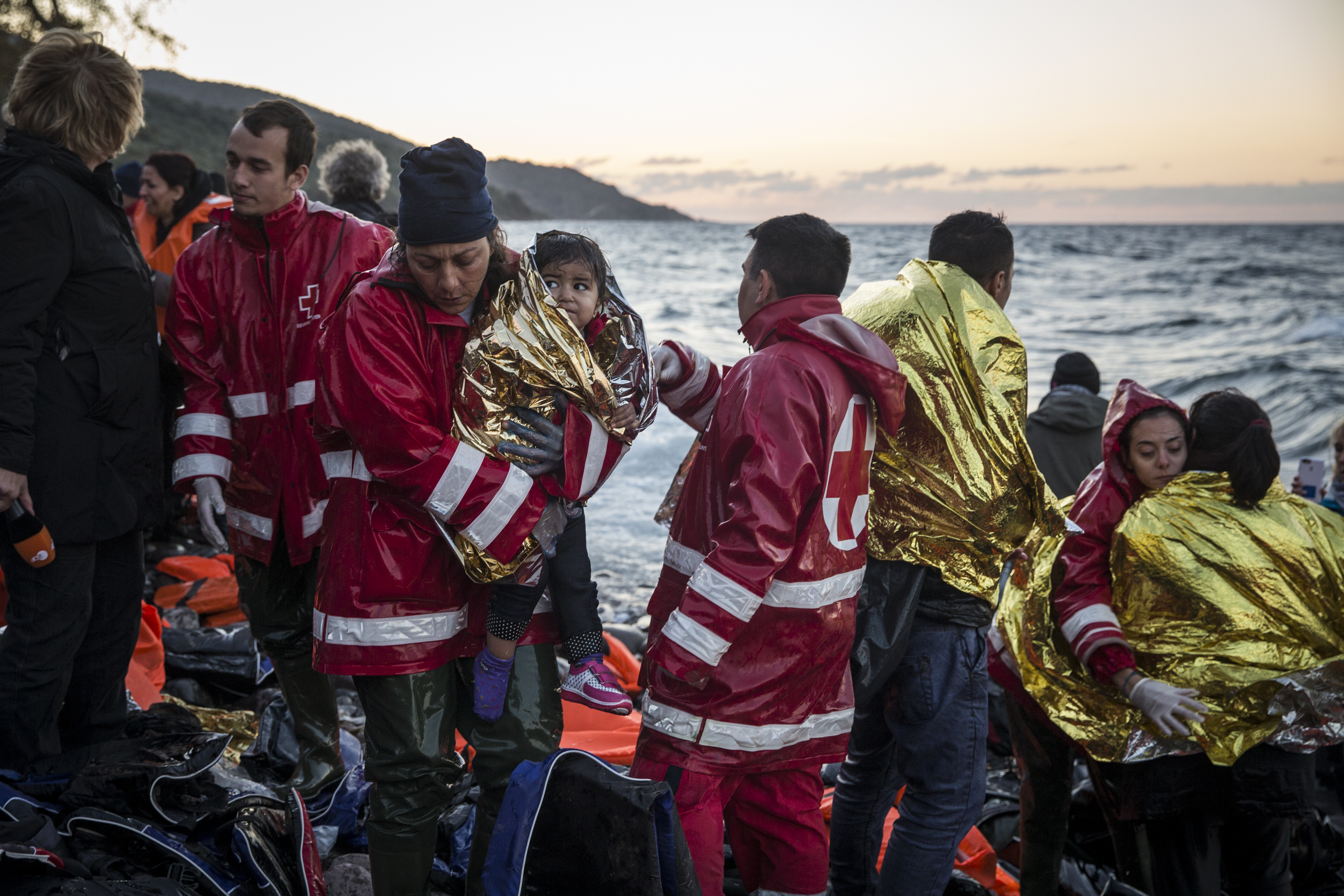 Volunteers try to warm migrants who have just come ashore on the Greek island of Lesvos near Skala Sikaminias