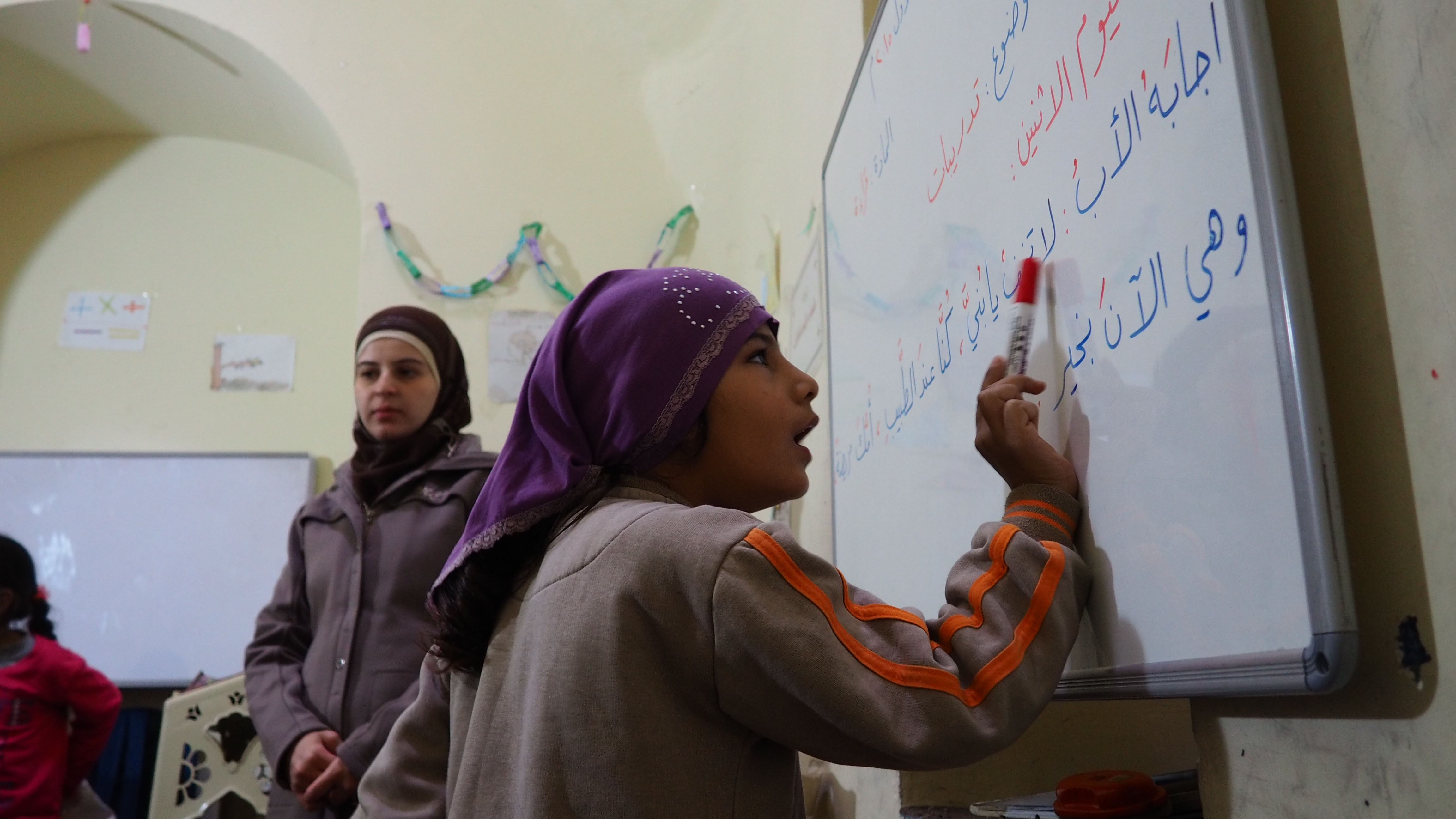 Inside a free school for Syrians hosted within a mosque in Istanbul, a mentally disabled child is asked to solve some Arabic grammar exercises in front of her class