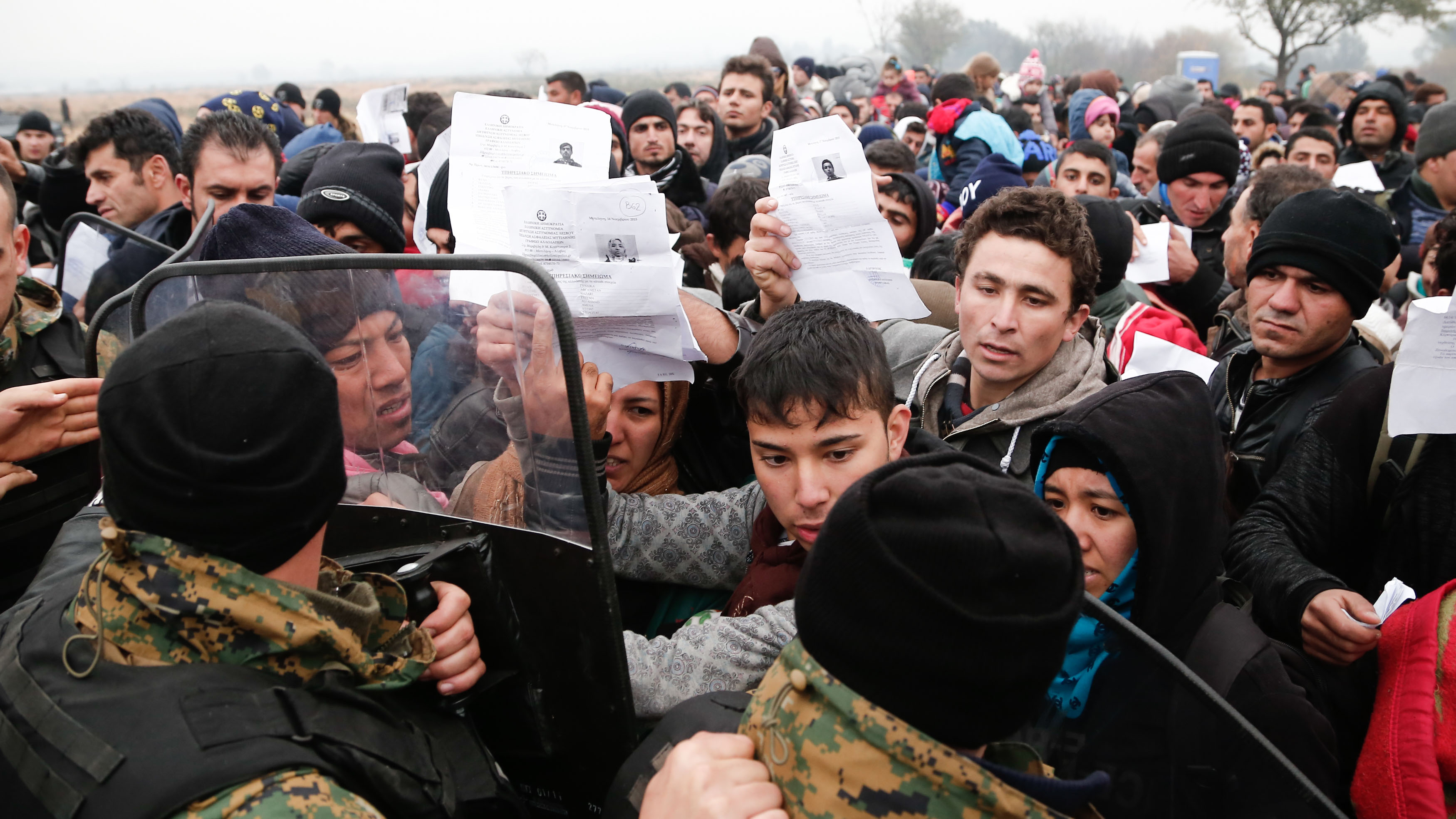 Migrants and refugees wave their Greek registration papers at the border with Macedonia where only certain nationalities were being allowed to cross.
