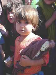 [Afghanistan] A small girl in Shaidayee IDP camp. During my six months stay in Herat this was the only time I saw a child with a doll. Normally IDP children only have self made toys.