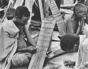 [Somalia] A group of Somali boys write Koranic verses on wooden boards at a traditional Madaras, Somalia, 4 December 2002. Over a decade of clan-based wars and devastating civil unrest has meant that two generations of young people have missed out on educ