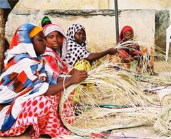 [Somalia] Somali women weaving baskets to be sold in the market.